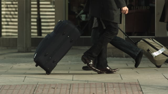 ms ts slo mo shot of below shoulder shot of man pulling suitcase in street / united kingdom - wheeled luggage stock videos and b-roll footage