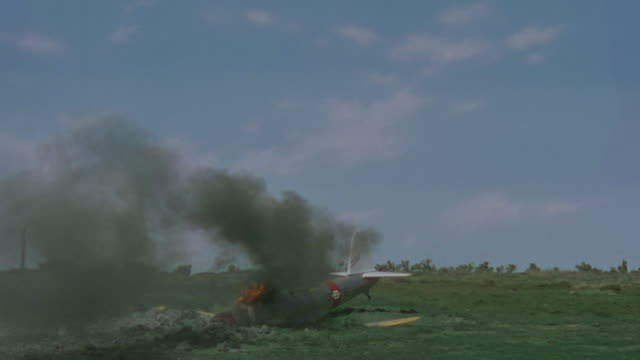 ms shot of bi plane crashing into empty field, plane catching on fire - airplane crash stock videos and b-roll footage