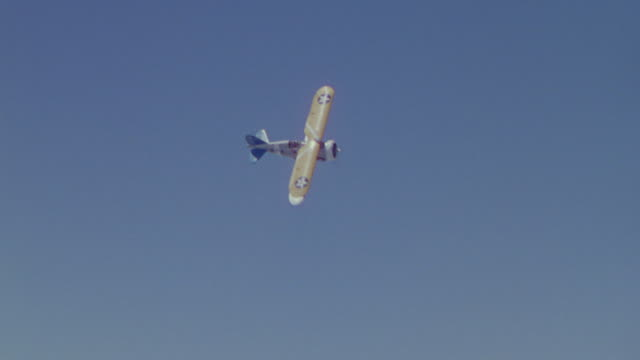 ms aerial ts td  shot of bi plane diving and maneuvering in and out of clouds - 複葉機点の映像素材/bロール