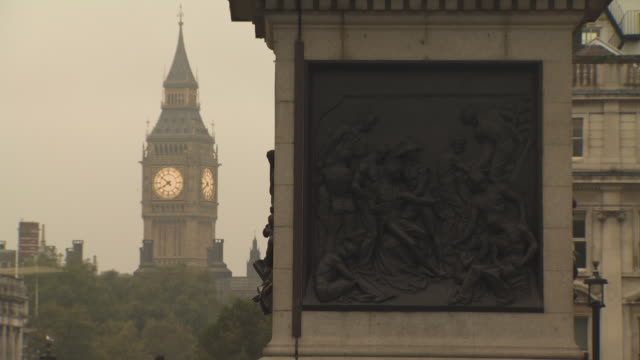 shot of 'big ben' standing behind the base of nelson's column in trafalgar square, london, uk. - nelson's column stock videos and b-roll footage