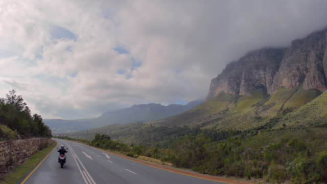 ws aerial shot of biker travelling along mountain pass / paarl, western cape, south africa - paarl stock videos & royalty-free footage