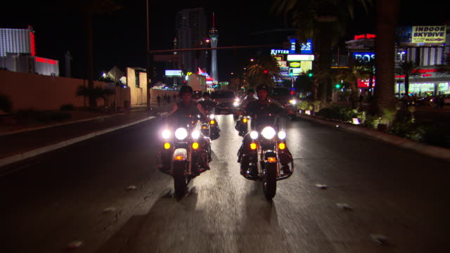 MS POV Shot of bikers moving in by traffic in city at night / Las Vegars, United States