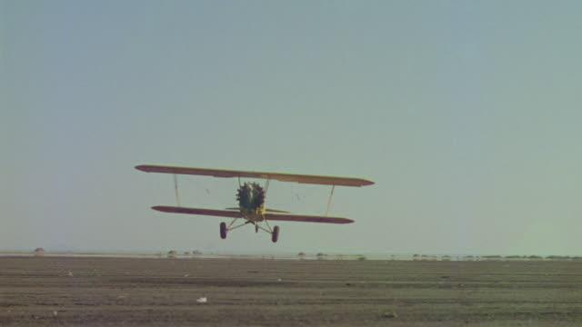 ms shot of biplane flying from back side - プロペラ機点の映像素材/bロール