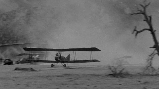 ms ts pan shot of biplane on fire briefly taking off and crashing on ground in airfield and people running toward burning plane - air vehicle stock videos & royalty-free footage
