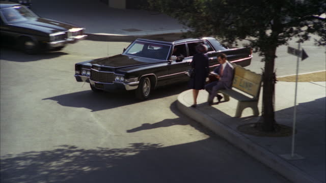 ms ts shot of black 1979 cadillac limousine comes around corner and being parked in front of store / los angeles, california, united states - limousine luxuswagen stock-videos und b-roll-filmmaterial