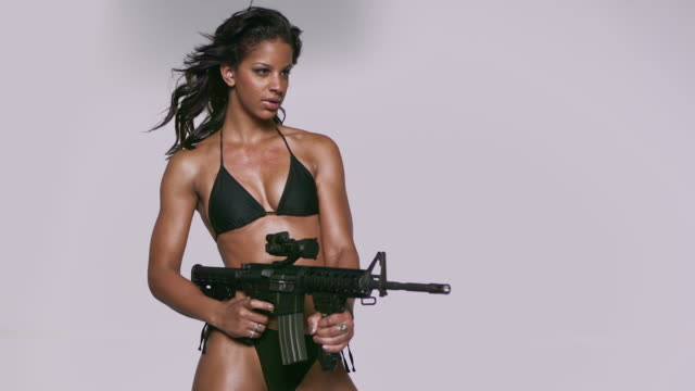 ms slo mo shot of black african american female firing mr27 machine gun, bullets coming out of side / studio, new york, united states - bikini stock-videos und b-roll-filmmaterial