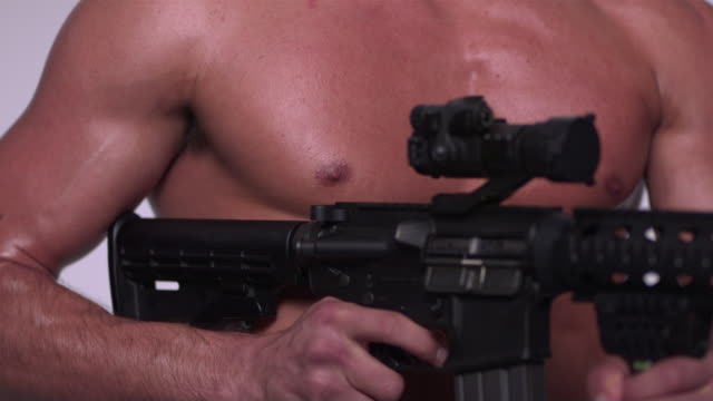 cu r/f slo mo shot of black african american male hand on trigger of mr27 machine gun in / studio, new york, united states - munition stock-videos und b-roll-filmmaterial
