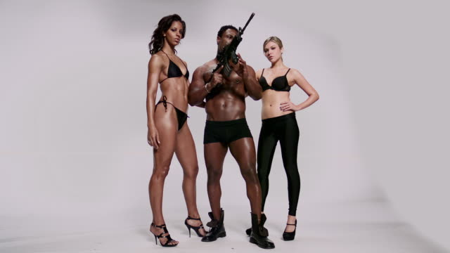 WS SLO MO Shot of black African American man shooting MR27 machine gun with two woman (maverick rifle) / Studio, New York, United States