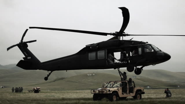 shot of black hawk helicopter attaching and hauling off humvee from field. - helicopter stock videos & royalty-free footage