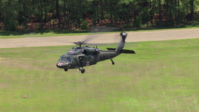 MS AERIAL ZO TS Shot of Black Hawk helicopter flying in air and landing at Camp Shelby military post in day light / Mississippi, United States