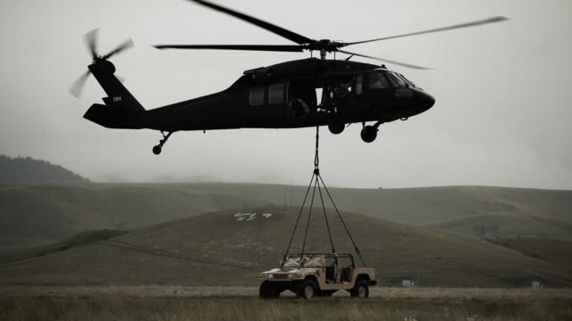 shot of black hawk helicopter hauling off humvee from field. - military helicopter stock videos and b-roll footage