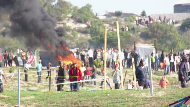 ws shot of black smoke rises from fire created by protesters during riot in mitchells plain township / cape town, south africa - demonstration stock-videos und b-roll-filmmaterial