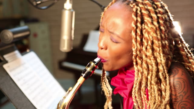 MS Shot of black woman playing saxophone in recording studio / Santa Fe, New Mexico, United States
