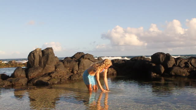 MS Shot of blonde woman pouring water from conch shell / Paia, Hawaii, United States