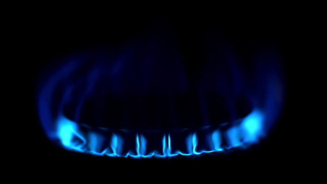 ECU Shot of Blue Flame from Gas Cooker against Black background / Calvados, Normandy, France
