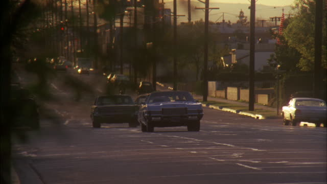 ms shot of blue four door sedan car (automobile) on residential street / los angeles, california, united states - 1972 stock videos and b-roll footage