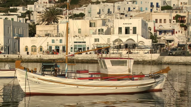 ms shot of boat on harbor of town during sunset / mykonos, cyclades, greece - mykonos stock videos & royalty-free footage
