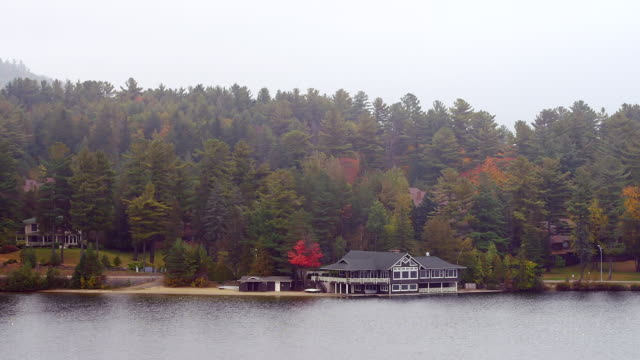 ws shot of boathouse along shore of lake with road running behind it / lake placid, new york, united states - lake placid town stock videos and b-roll footage