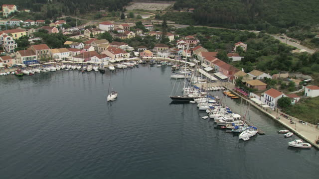 stockvideo's en b-roll-footage met ws aerial ts zi shot of boats anchored in fiscardo at small harbour village in fiscardo / kefalonia, ionian islands, greece  - anchored