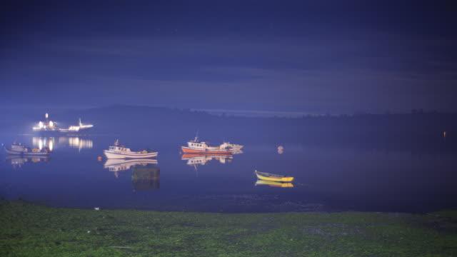 vídeos de stock e filmes b-roll de ws t/l shot of boats anchored in lake and multiple lights flashing at night / chonchi, isla grande de chiloì©, chile - ancorado