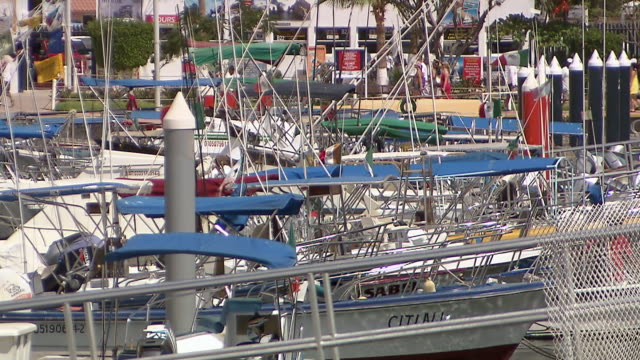 MS PAN Shot of boats in marina and lots of small Mexican flags attached to boats with people walking / Cabo San Lucas, Baja California Sur, Mexico