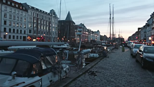 ms slo mo shot of boats in marina with buildings on either side at sunset / copenhagen, denmark - oresund region stock videos & royalty-free footage