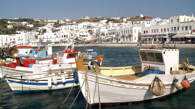 ms shot of boats moored at jetty with houses on hill / mykonos, cyclades, greece - mykonos stock videos and b-roll footage