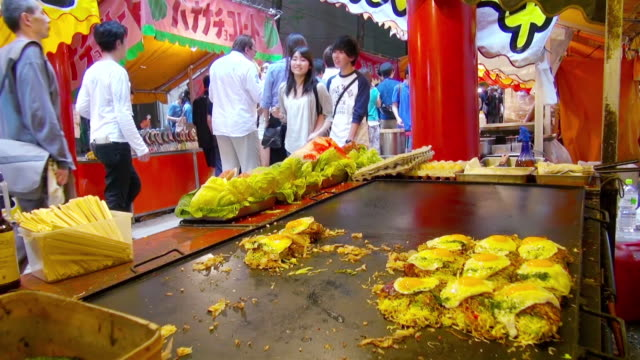 MS Shot of Booth selling Okonomiyaki, (egg, shredded cabbage with vegetables, held together with a thin batter) sold at Hanazono Festival / Tokyo, Japan.