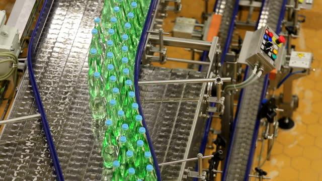ms shot of bottle moving in bottling plant at beverage industry / gerolstein, rhineland palatinate, germany  - コンベヤーベルト点の映像素材/bロール