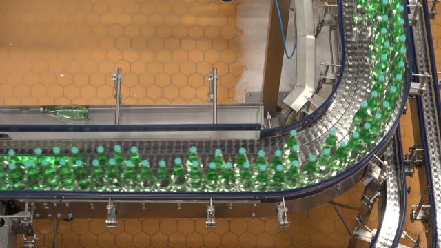 ms shot of bottle moving in bottling plant at beverage industry / gerolstein, rhineland palatinate, germany  - plastic cap stock videos & royalty-free footage