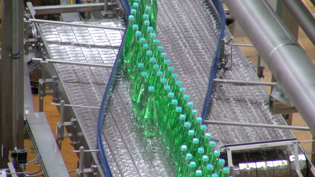 ms shot of bottle moving in bottling plant at beverage industry / gerolstein, rhineland palatinate, germany  - 繁栄点の映像素材/bロール