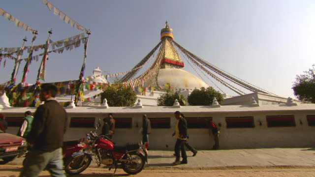 ms pan shot of boudhanath stupa temple with people / kathmandu, nepal - stupa stock videos & royalty-free footage