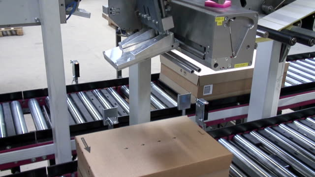 MS Shot of Box moving on conveyer belts in warehouse and attatched barcoad on box / Hamburg, Germany