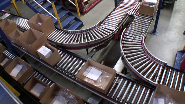 ms shot of box moving on conveyer belts in warehouse / hamburg, germany - laufband stock-videos und b-roll-filmmaterial
