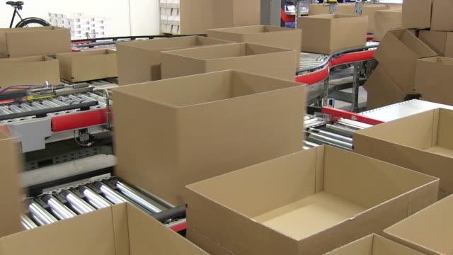 vídeos de stock e filmes b-roll de ms shot of box on conveyor belt at warehouse of mail order company / grossostheim, bavaria, germany - caixa de papelão