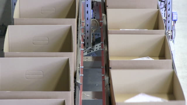 MS Shot of box on conveyor belt at warehouse of mail order company / Grossostheim, Bavaria, Germany