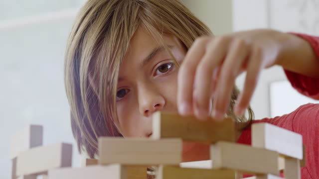 cu shot of boy adds finishing touches to his wooden structure  / london, hampstead, united kingdom - toy block stock videos and b-roll footage