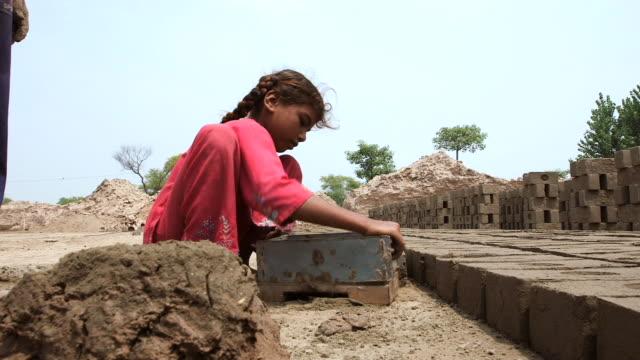 MS Shot of boy and girl constitute handmade bricks / Old city of Lahore Punjab Pakistan