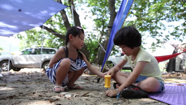 Shot of boy and girl playing with toy hammer at Camping Site