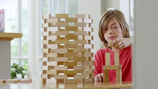 MS PAN shot of Boy building wooden tower with building blocks / London, Hampstead, United Kingdom