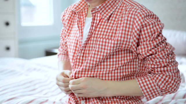 ms tu shot of boy buttoning up shirt in bedroom / london, greater london, united kingdom - oberhemd stock-videos und b-roll-filmmaterial