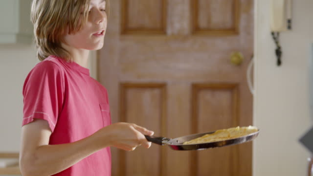 ms slo mo shot of boy flipping his freshly made pan cake / london, hampstead, united kingdom - pancake stock videos & royalty-free footage