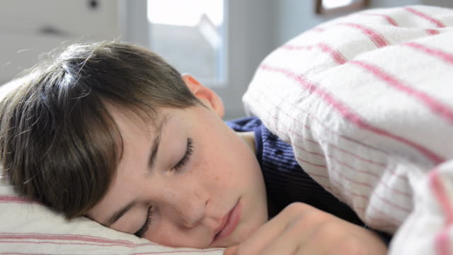 cu shot of boy looking tired in bed / london, greater london, united kingdom - blanket stock videos and b-roll footage
