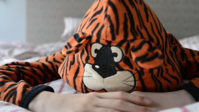 CU Shot of boy looking tired in bed wearing tiger pyjamas / London, Greater London, United Kingdom