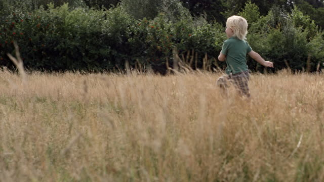 ms pan slo mo shot of boy playing through grass field - focus on background stock videos and b-roll footage