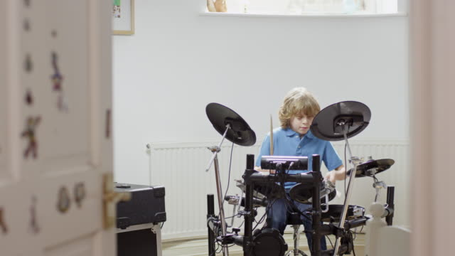 ms pan shot of boy practicing drumming while in his bedroom / london, hampstead, united kingdom - drum percussion instrument stock videos & royalty-free footage