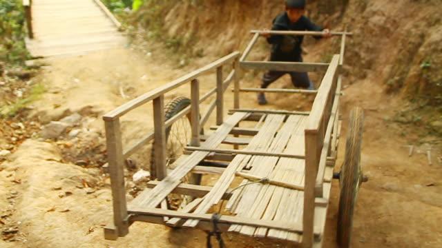 ms ts r/f slo mo shot of boy pushing small wooden cart on irregular ground / mountain village near muang ngoi, luang prabang, laos - cart stock videos & royalty-free footage