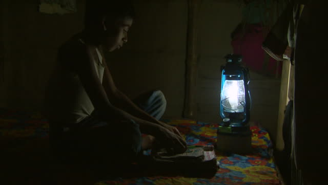 MS Shot of boy reading aloud by rechargeable lamplight / Pabna, Bangladesh