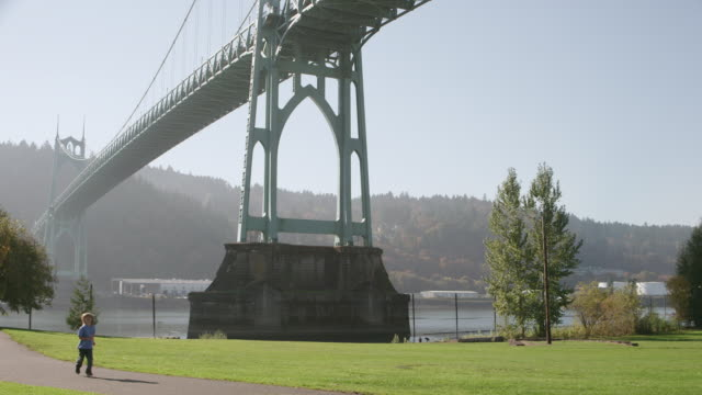 WS PAN Shot of boy running through park as large St. Johns bridge looms behind him / Portland, Oregon, United States