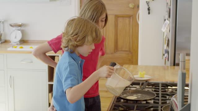 vídeos y material grabado en eventos de stock de ms ts shot of boys working as team to cook pancakes together in kitchen / london, hampstead, united kingdom - rebozado